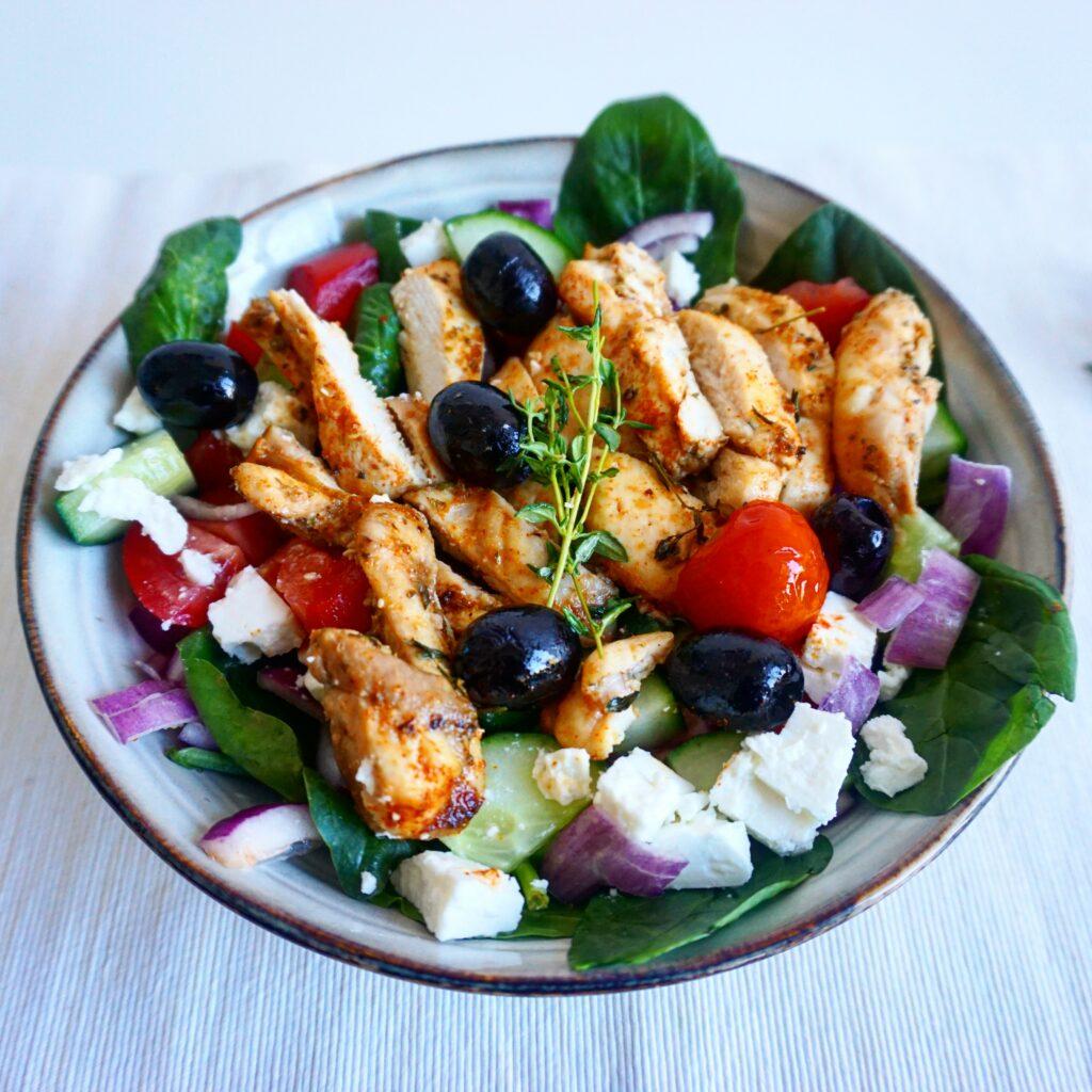 Griekse salade met spinazie, feta en gemarineerde kip uit de oven