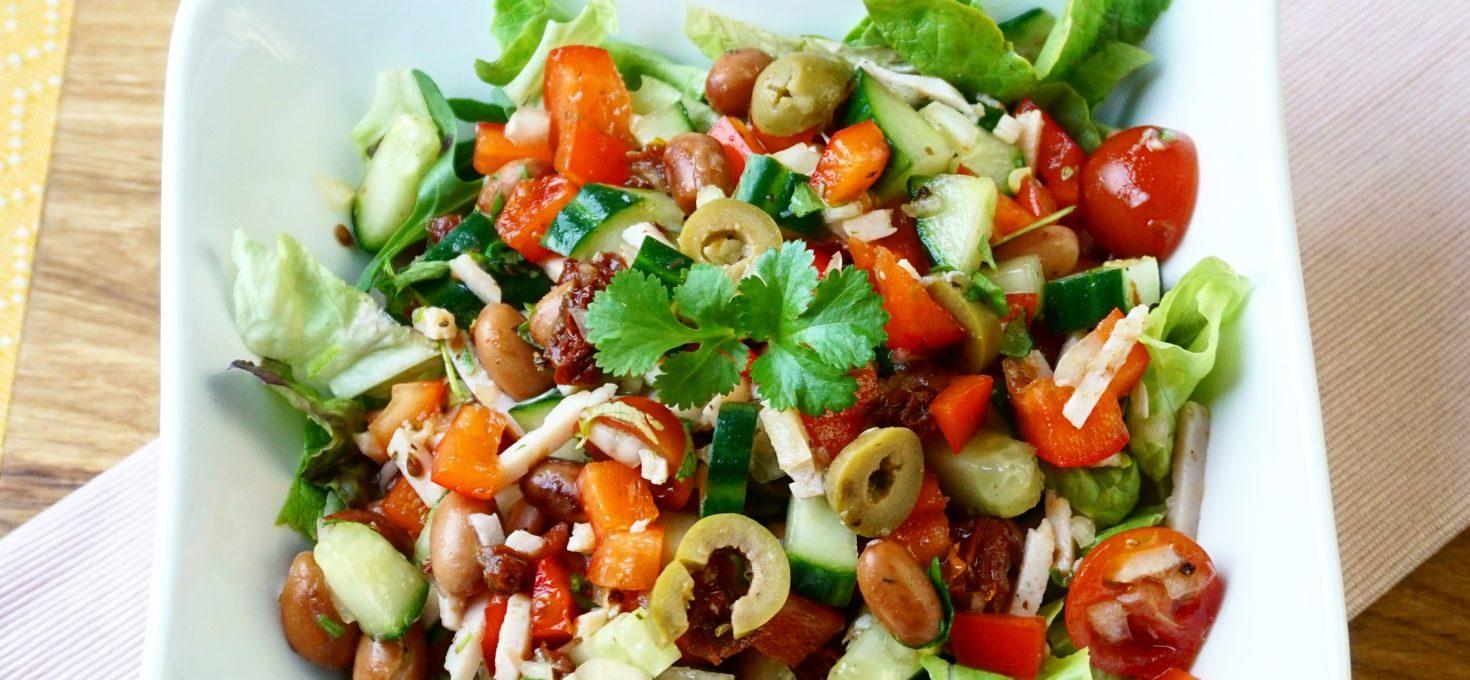 Mediterraanse salade met kip, bonen, zongedroogde tomaat en olijven